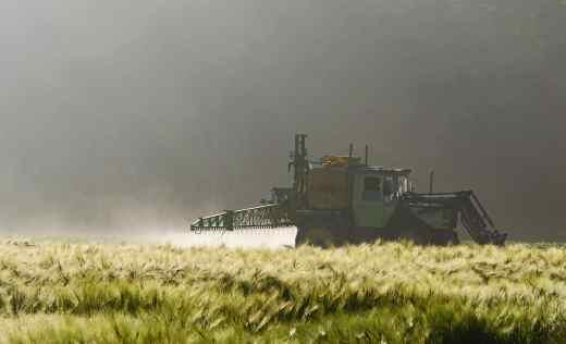 Landmaschine versprüht breitflächig Subsanzen auf ein Feld
